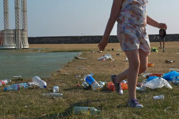 Girl walks through plastic waste