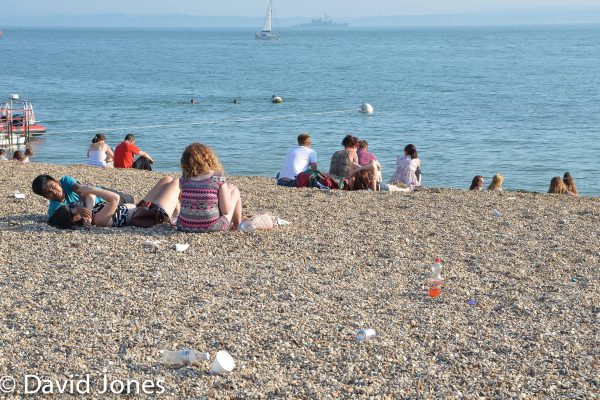 Sitting on the beach covered in plastic pollution